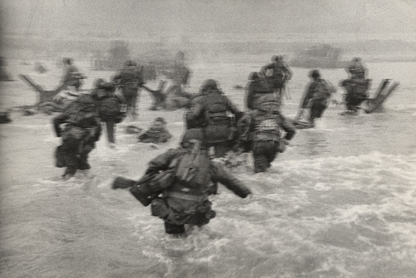 Photo of US Soldiers wade into shore at Omaha