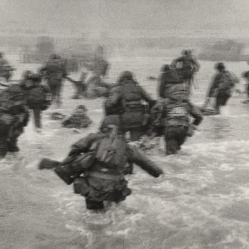 US Soldiers wade into shore at Omaha